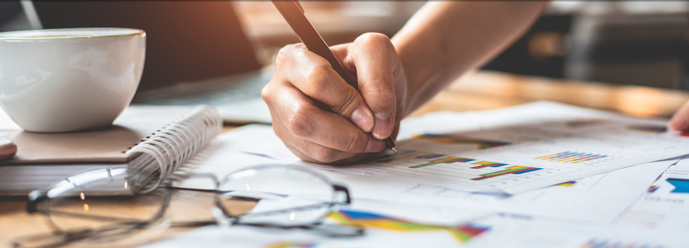 Bookkeeper writing on paper like at Complete Bookkeeping by Andrea